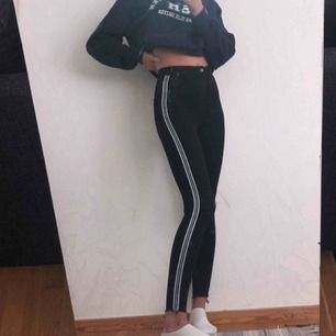 högmidjade svarta tighta jeans med vit, grön, blåa streck på sidan av benen, slitna nere vid anklarna, längden på jeansen sitter bra på mig som är 168 men går absolut att klippa kortare eller vika upp köpare står för frakt
