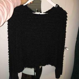 En svart fin tröja med öppen slits i ryggen