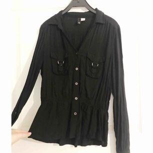 Svart skjorta med resår i midjan och fickor på bröstet. Från H&M. Storlek 38 men passar 34/36.