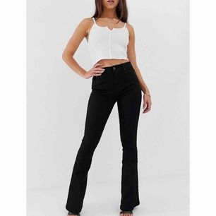 Svarta utsvängda jeans från Asos, använda en gång. Storlek 26/30.