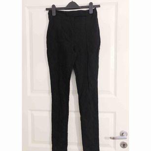 Svarta tighta kostymbyxor med pressveck, från Asos i storlek 36.