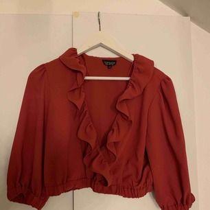 Croppad blus inlöpt i London. Använde denna till en hög kjol och det passade så bra! Säljes pga. Ingen användning. Färgen är mer som den andra bilden, alltså lite mer rosa. Mjuk i materialet. Frakt tillkommer.