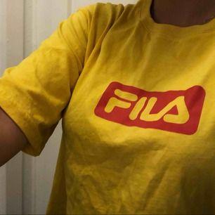 En gul Fila t-shirt med röd text. Sparsamt använd. Är en crop top men blir mer som en vanlig t-shirt för mig som egentligen brukar ha S. Kan mötas upp i Uppsala eller skicka. Köpare står för frakt. Tar swish eller kontant💕