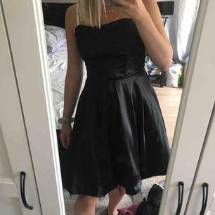En svart (blank svart) lite kortare klänning utan axelband.  Volanger med nät tyg nertill. Aldrig använd!