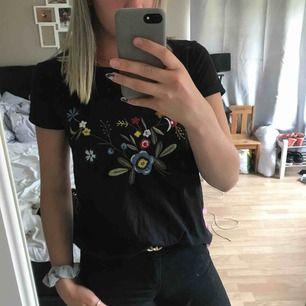 Snygg svart T-Shirt med blommor på.