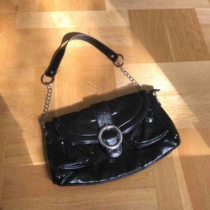 Liten handväska köpt secondhand men i superbra skick! Svartglansig med silvriga detaljer och mycket utrymme! Köparen står för frakt kostnader!🥰