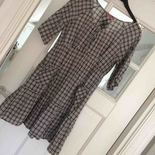 Midilång vid klänning från indiskamed fickor och rutigt mönster. Snygg med skärp i midjan eller som den är.  Frakt står köparen för!