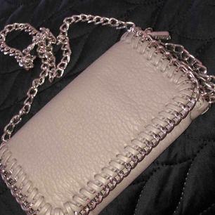 En grå väska med kedja. Väskan är i fint stick och har bara använd några fåtal gånger. Köparen står såklart för frakten