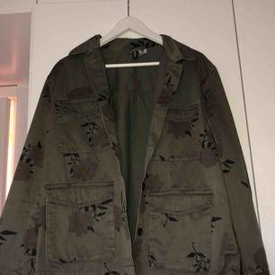 Militärgrön, blommig jacka ifrån H&M. Aldrig använd och är som ny. Köparen står såklart för frakten:)