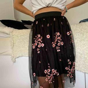 Svart kjol med mesh-tyg med broderade körsbärsblommor, insydd underkjol. Storlek M, perfekt skick prislapp är kvar.