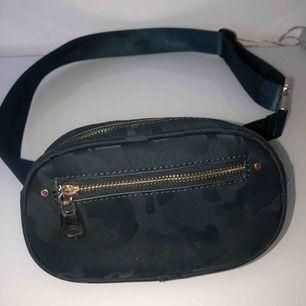 Beltbag från Zara Australien (säljs inte i Sverige) Har ett ganska svagt grått och svart camo print och gulddetaljer.