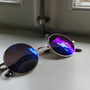 Solglasögon från Zebra A/S med guldram och blålila reflekterande glas. UV.