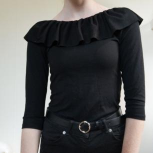 Svart body från Zara i bekvämt trikåmaterial med 3 starka knappar. Volang och 3/4 arm. Som ny.