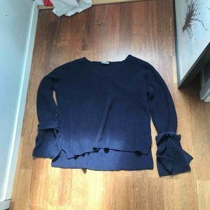 Jättefin marinblå stickad tröja med knytdetaljer på ärmarna!