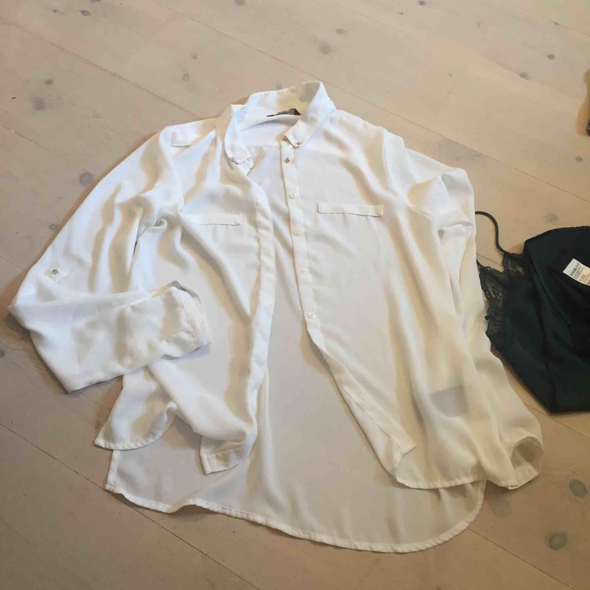 En vit, luftig skjorta. Man kan piffa upp den på olika sätt med knapparna på ärmarna, se första och andra bilden. Storlek står inte, men man kan knyta den så den bli mindre och ha den löst så passar den de flesta. . Blusar.