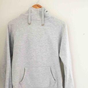En grå turtleneck hoodie. Den är väl använd och har några mindres skavanker, såsom bortskavd färg på snörena.  Perfekt till hösten.