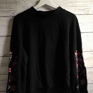 En långärmad svart tröja med vida ärmar som är dekorerade med broderande blommor! En tröja som både värmer och ser bra ut, har använts kontinuerligt  men är fortfarande i bra form. Frakt 25kr😊