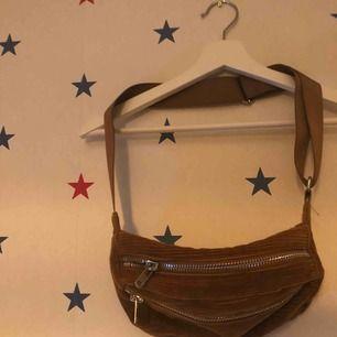 En brun manchesterväska ifrån weekday. Ofta använd men inget som syns på väskan.