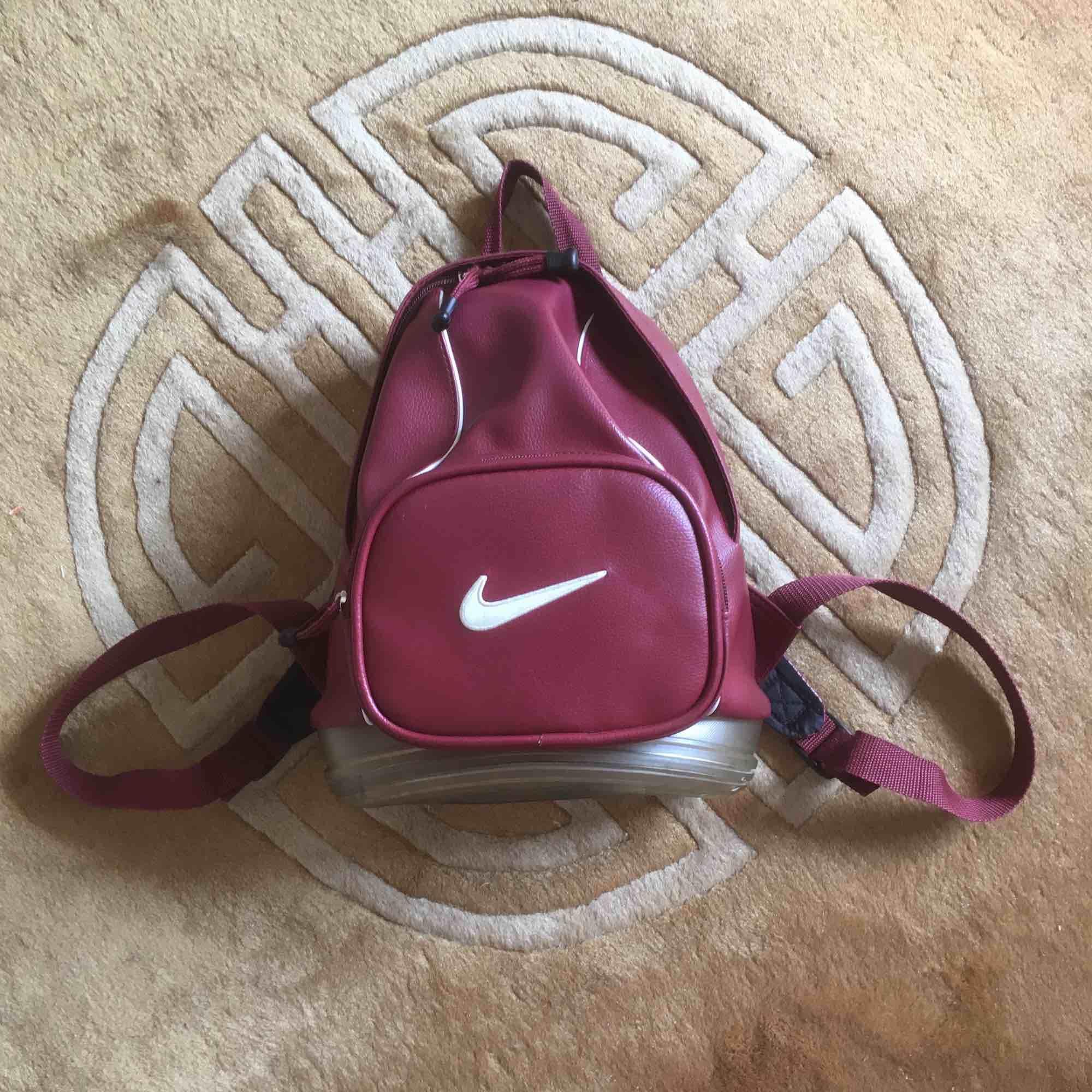 Cool Nike-ryggsäck. Inte så stor, inte heller liten. Mått: 25x35 cm. Små färgfläckar i botten( se bild 2 och 3)  men syns ej utåt!. Väskor.