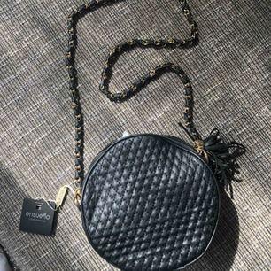 Helt oanvänd väska i svart läderimitation & guldkedja. Köptes i Spanien för 11 euro. Kan mötas upp i Stockholm annars tillkommer frakt!
