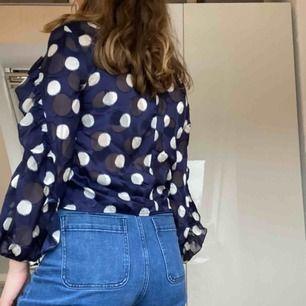 Mörkblå blus med vita prickar från Zara. Den har volang på ärmarna och omsluts med 2 knappar i kragen. Aldrig använd. Frakt tillkommer. Skriv för mer info.