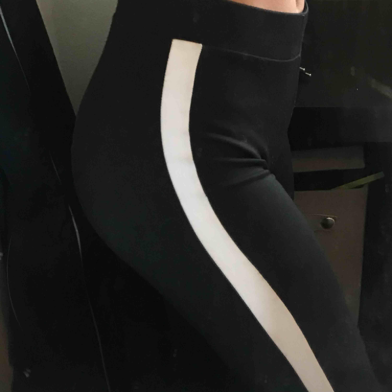 Svarta utsvängda Yoga pants från GinaTricot med vita sträck längst sidan av benen.  Storlek XS men passar också S Fint skick  Köpare står för frakt☺️. Jeans & Byxor.