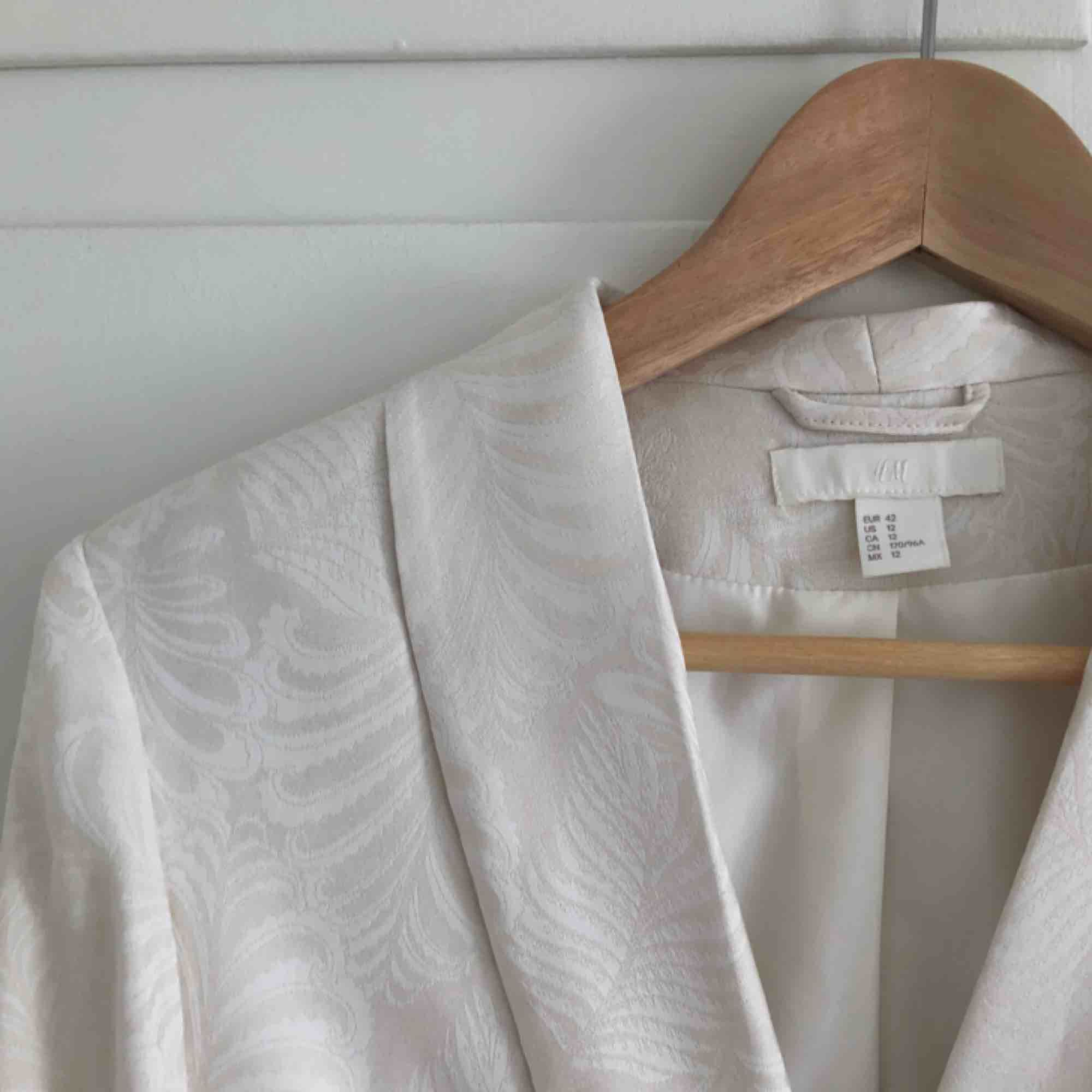 Vit kavaj från H&M, med snörning i midjan. Aldrig använd är stl 42 funkar som oversize för stl38&40.. Kostymer.
