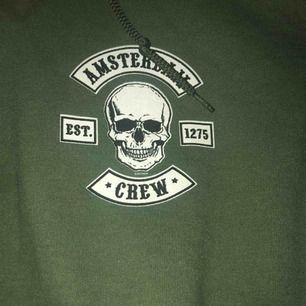 """Skitfin hoodie med """"amsterdam crew"""" på både bröst och rygg. Frakt ingår ej i pris."""