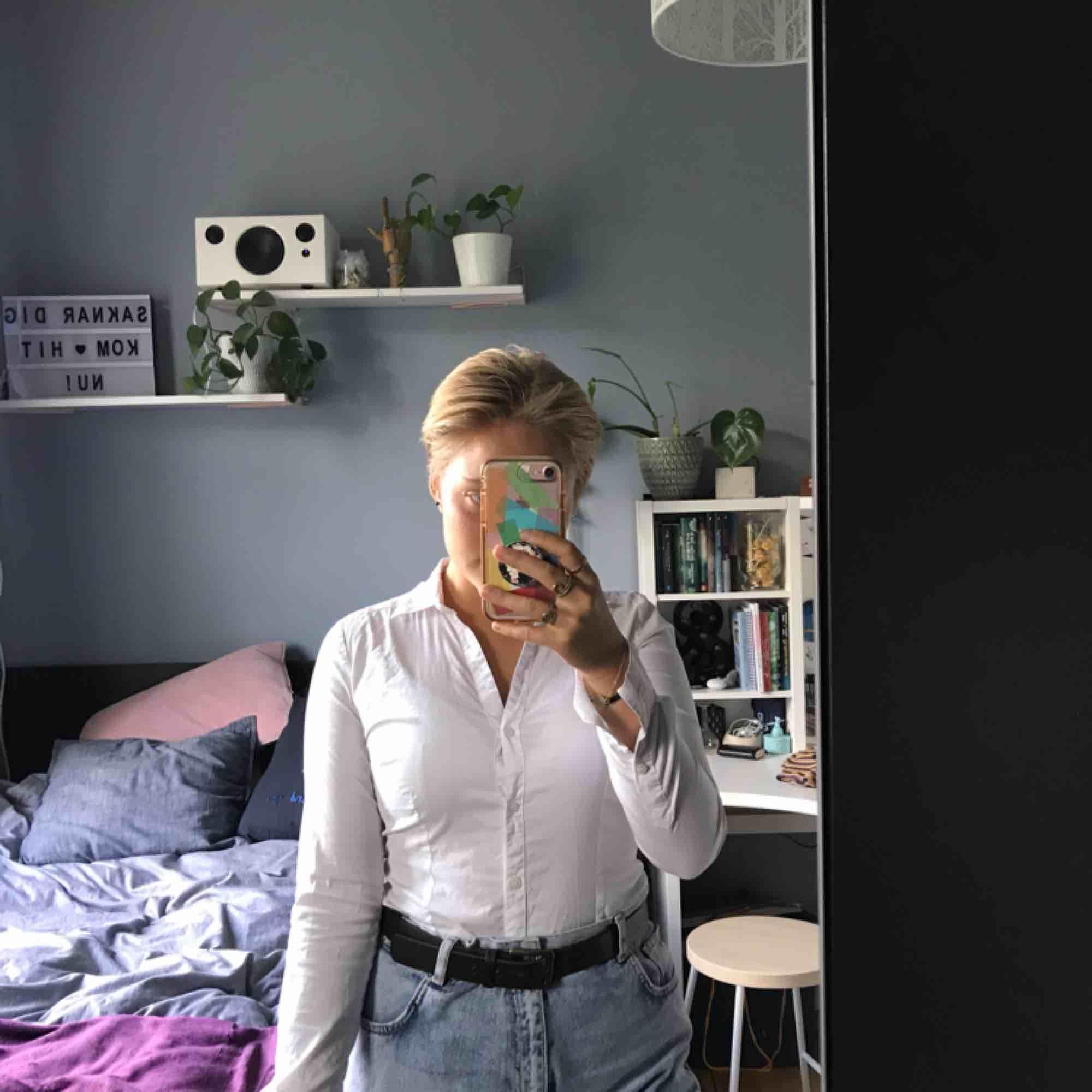 """En supersnygg vit skjorta från H&M, den är """"V-ringad"""" (går inte att knäppa hela vägen upp), den är superstretchig och figursydd så den lägger sig väldigt fint på. Säljer då den tyvärr blivit för liten.. Skjortor."""