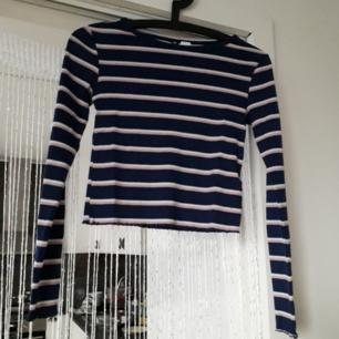 Ribbad o randig cropped långärmad tröja från HM! Den har små petita volangdetaljer i utkanten av ärmarna och nedanför tröjan(där den är skuren-cropped/kort). Frakt: 42:- Postens S-emballage
