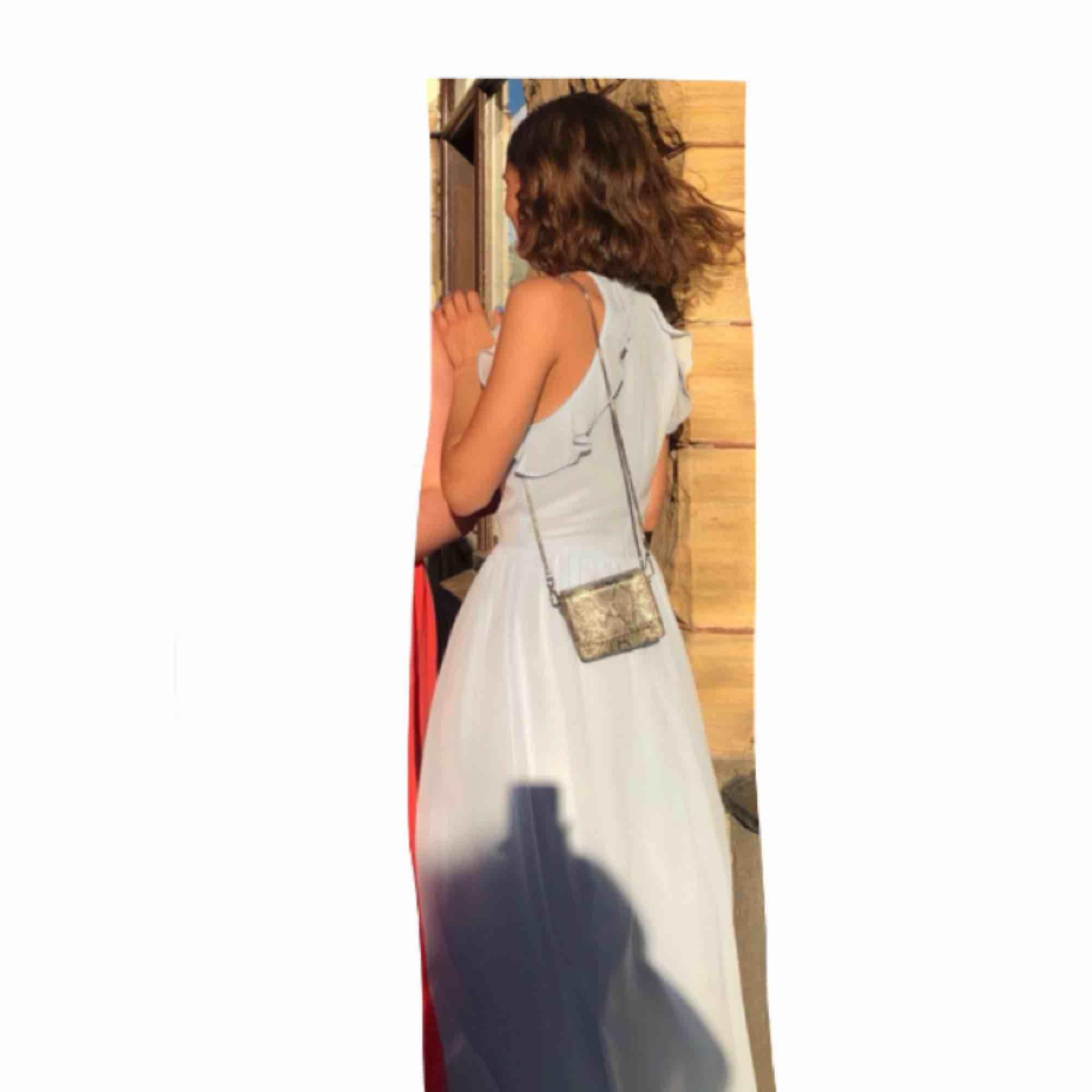 Superfin ljusblå långklänning. Jag hade den på min bal men den funkar självklart vid andra tillfällen också. Den är från H&M. Jag är ca 161 cm och den var perfekt längd till klackar (8 cm). Endast använd en kväll, gott skick!. Klänningar.