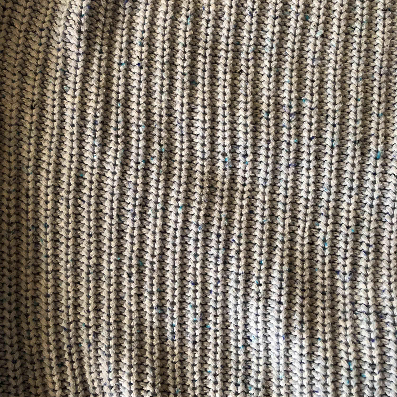 Ljusblå stickad tröja med vida armar. Små prickar av andra nyanser av blå i.. Stickat.
