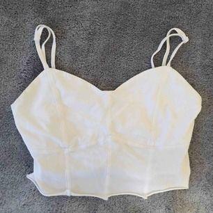 Jättefint vitt croppat linne i fint skick💕 Sparsamt använd. Även justerbara band.