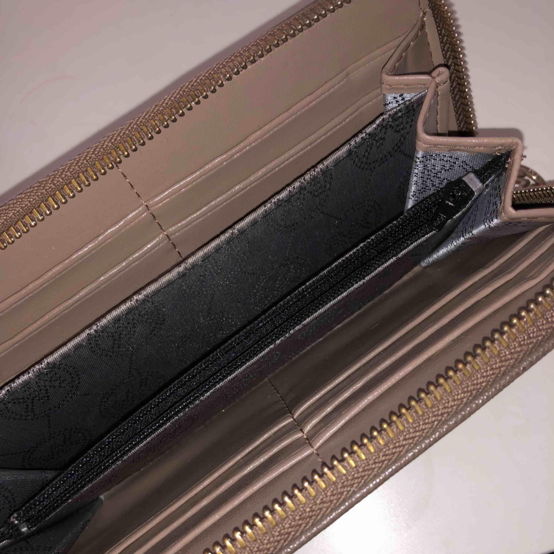 Helt ny oanvänd mk plånbok i färgen nude/biege . Accessoarer.