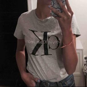 Grå t-shirt från Calvin Klein jeans. Lite slitningar på trycket men ingenting som syns när man använder den. Nypris: 499 kr på Jolina. Säljer på grund av att den inte passar längre. Frakt ingår i priset!