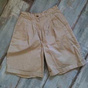 Ett par jättesöta högmidjade shorts från Kappahl!! Aldrig använda:)  100% bomull och väldigt fint tyg med bra kvalité och skön textur! Lite oversized modell vid benen.  Färgen syns bäst på bild 2 och 3, i första är den lite för rosa.  Kan tyvärr inte visa bild på då de är för små på mig! Byxorna har knapp (+extraknapp), dragkedja och öglor för bälte!:) Jag säljer även ett par liknande byxor i ljusrosa<3