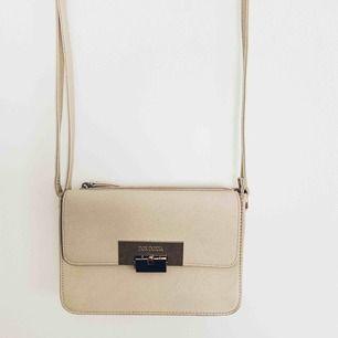 Handväska med justerbart axelband i beige färg med gulddetaljer, väskan har tre rymliga fack 🍂🍁