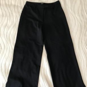 Svarta vida kostymbyxor/slacks i stl 38 från Sisters. Använda en gång och i jättefint skick. Frakt 59 kr.
