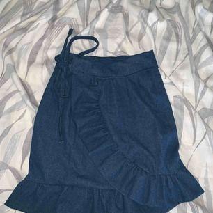 Jättefin omlott kjol i jeans tyg med volang detaljer som man knyter i sidan. Passar Xs-M eftersom den är justerbar! Pris kan diskuteras