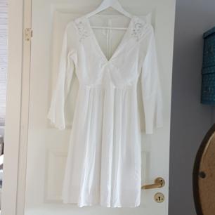 Fin vit sommrig klänning med V-ringning, öppen rygg, utsvängda ärmar, spets och knytning i ryggen. Köpt för 400, använd 2-3 ggr. Köparen står för frakt men kan även mötas upp i stockholm.
