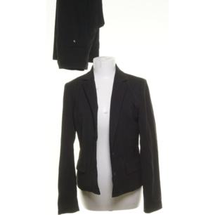 Svart smalstrecksrandig kostym från Inwear i ull-blandning. Stl 38 på kavajen och stl 36 på byxorna som är en vid avslappnad modell. Frakt 63 kr.