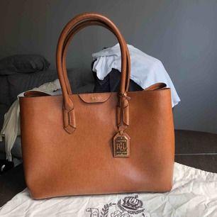 En Lauren Ralph Lauren väska i superfint skick! Knappt använd! Köpt på NK, väskpåse ingår. Kan hämtas upp i Stockholm stad eller postas, då tillkommer frakt.