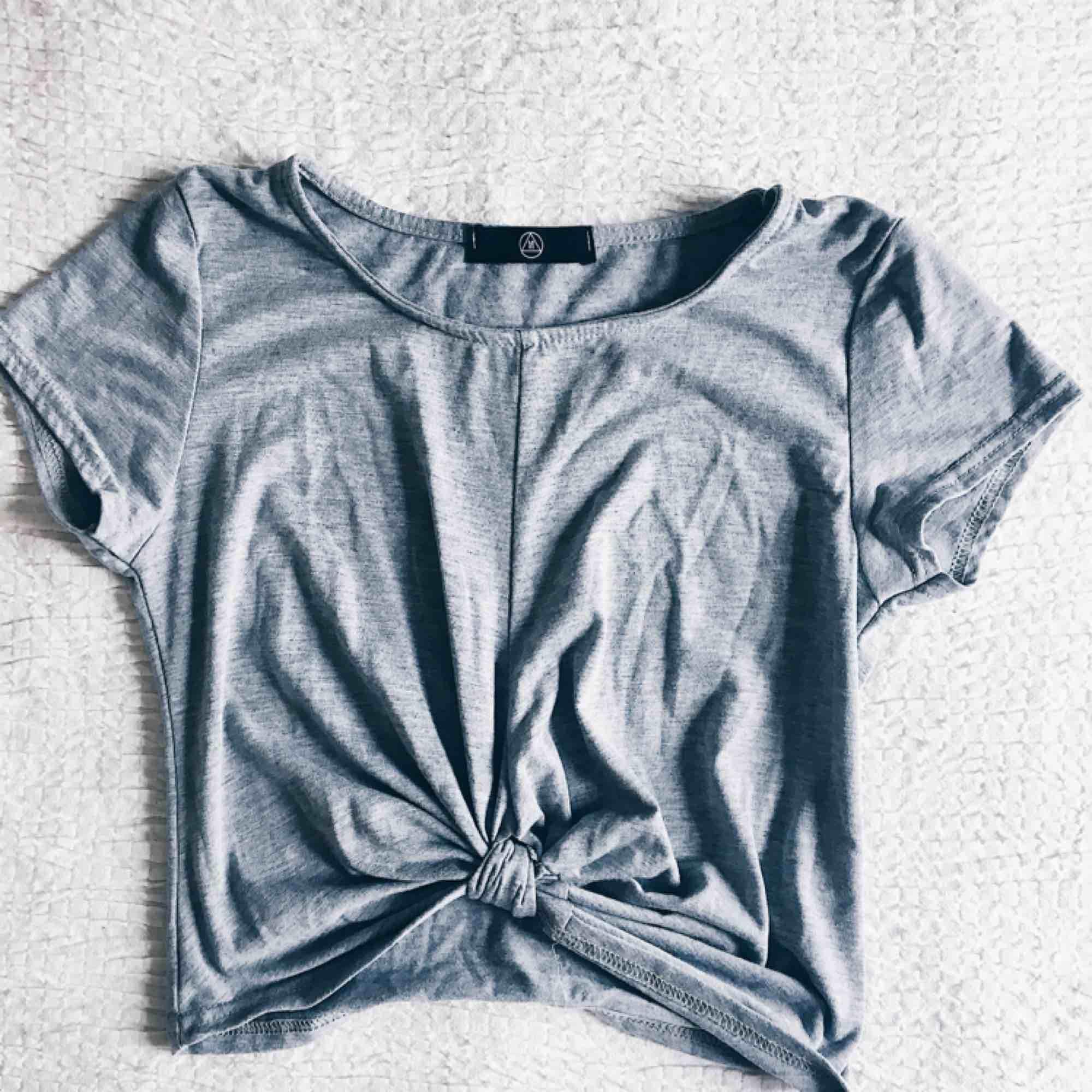 T-shirt från missguided. Knuten är fastsydd och ger en smickrande figur. Väldigt sparsamt använd så snälla ge denna fina tisha ett nytt hem! :) . T-shirts.