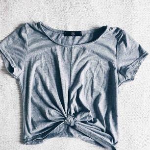 T-shirt från missguided. Knuten är fastsydd och ger en smickrande figur. Väldigt sparsamt använd så snälla ge denna fina tisha ett nytt hem! :)