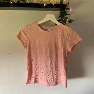 Ljusrosa t-shirt med pärlor på. Använd 1 gång. I mycket bra skick. Säljer på grund av att jag inte använder den.