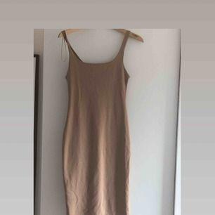En bech lång klänning som sitter tajt. Den har en slit längst ner på baksidan under rumpan. Köparen står för frakten
