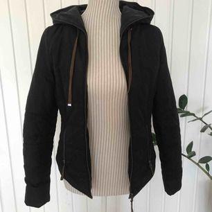 En fin svart jacka med bruna detaljer i storlek XS. Dragkedjan går att dra hela vägen upp. Frakt på 80 kr tillkommer