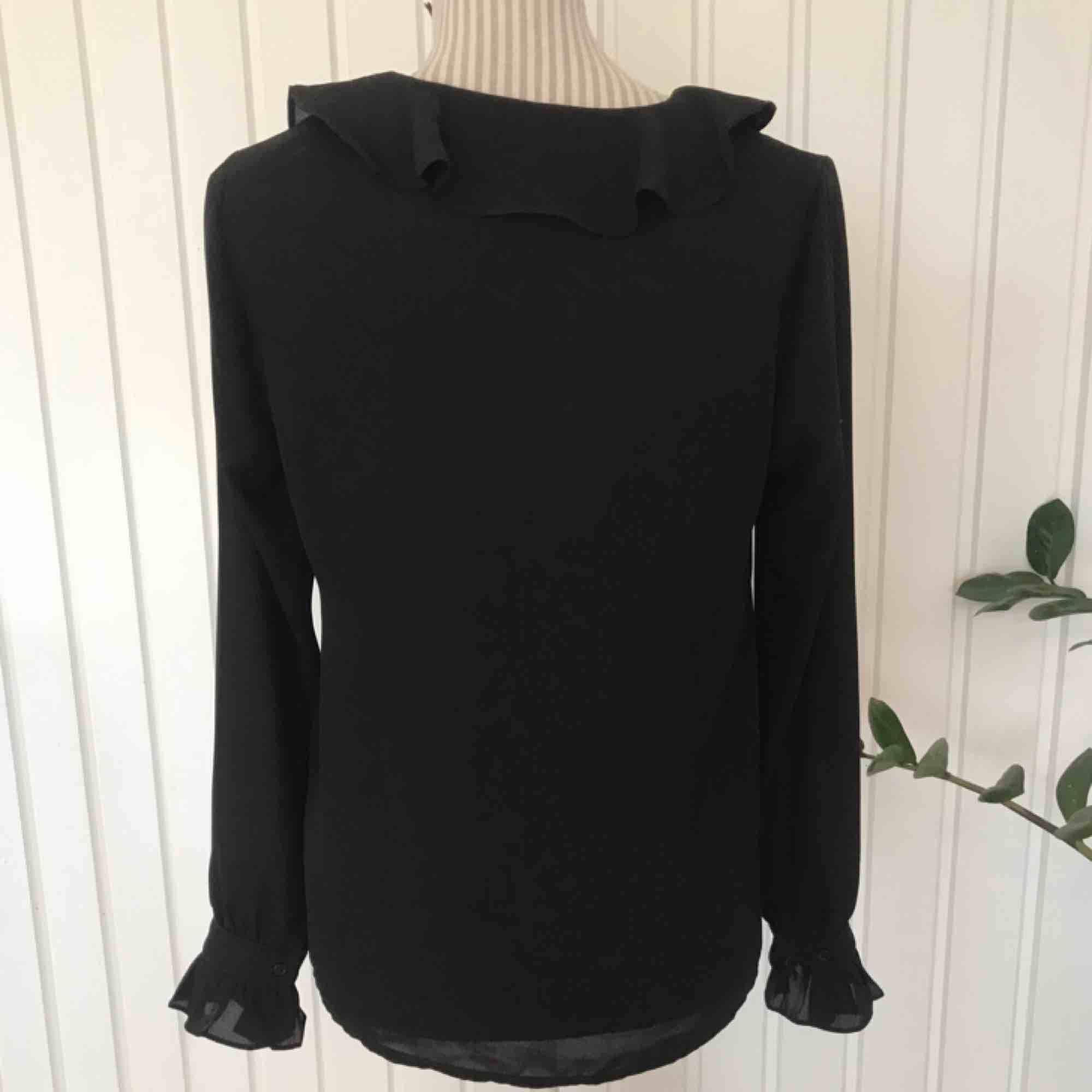 Supersöt svart blus med volanger från Ginatricot i fint skick! Frakt på 40 kr tillkommer. Blusar.