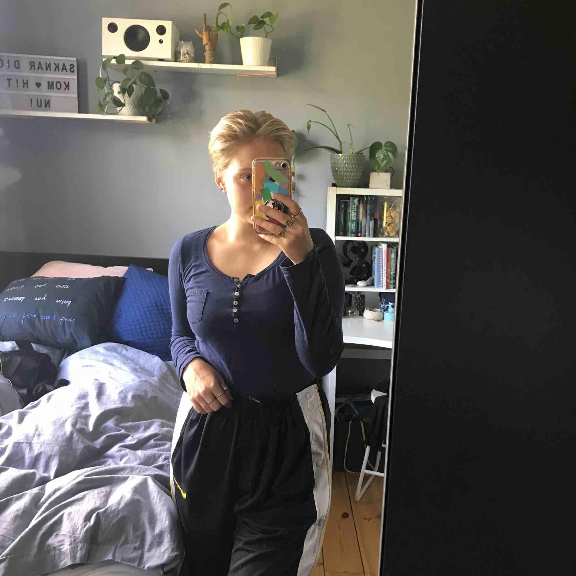 En marinblå, långärmad, tunn tröja med en liten fika på de vänstra bröstet. Tunn o skönt tyg. Storlek M, men den passar S också. . Tröjor & Koftor.