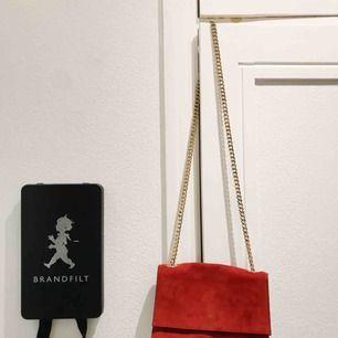 """Röd snygg väska från Zara! I mocka med guldig kedja. Fint skick, enda märkbara är en viss färgförändring där den """"knäpps"""" ihop(stängs med magnet). Snyns knappt men finns där om man ser efter nära. Köpt för ca 600kr. Frakt 59kr!"""
